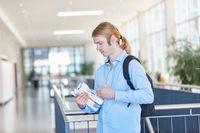 Student mit einem Stapel Büchern