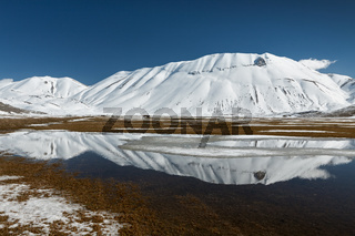 Sibillini mountains reflected in the water with snow