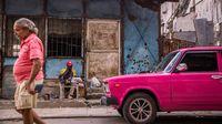 Man with pink Oldtimer im Havana, Cuba