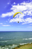Paraglider over sea with blue sky