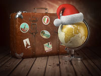 Christmas or new year travel concept. Old suitcase with globe nad santa hat on wood  background.