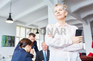 Frau als Chef steht selbstbewusst vor Team