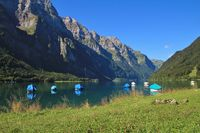 Green meadow at lake Klontalersee. Fishing boats and mountain range Glarnisch. Summer scene in Switzerland.