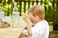 Kleiner Junge trinkt Milch aus der Müslischale