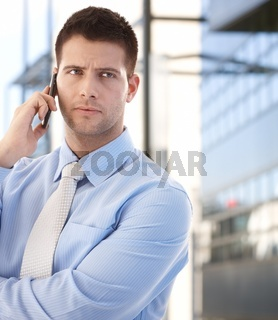 Confident businessman using mobile outdoors