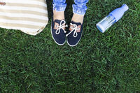 Feet of a young girl on a background a green grass with bottle of water and bag