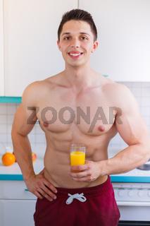 Bodybuilder junger Mann trinkt trinken Orangensaft Saft Hochformat gesunde Ernährung