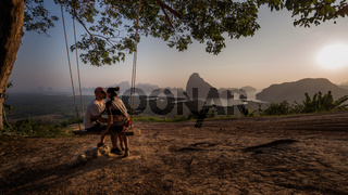 Couple on the bench over beautiful tropical mountain landscape