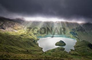 sunrays through clouds over alpine lake