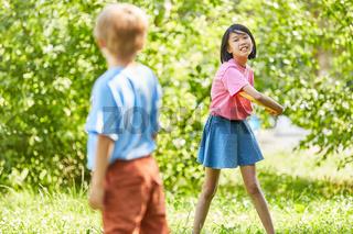 Zwei Kinder spielen Frisbee im Sommer