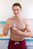 Gesunde Ernährung junger Mann essen Joghurt Bodybuilder in der Küche Hochformat Frühstück