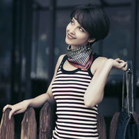 Happy young fashion woman in striped tank top with handbag