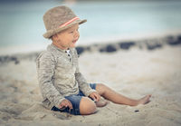 Child looking looking into the distance on the beach