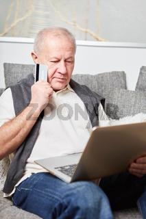 Senior mit Laptop PC beim Shopping
