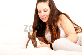 Caressing a rabbit in bed