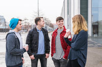 group of young adult friends having a conversation while standing together on city street