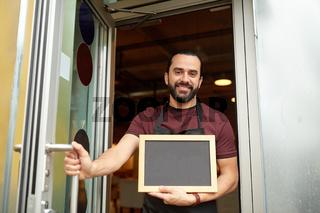 man or waiter with blackboard at bar entrance door