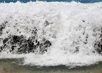 Frozen motion of ocean waterfall over rocks at Lumahai Beach