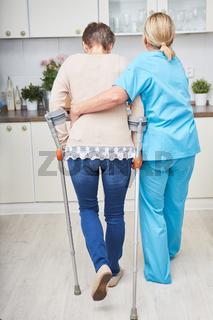 Alte Frau trainiert mit Krücken zu laufen