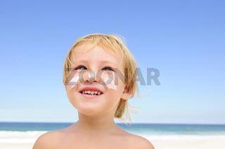 Sommerferien: Kind mit Sonnencreme im Gesicht am Strand