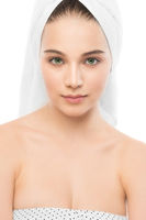 Beautiful young brunette woman with clean face and towel on her head. Isolated.