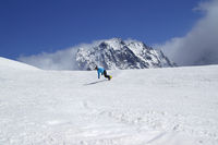 Snowboarder downhill in high snowy mountain