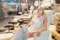 Woman shopping for new rocking chair in furniture store.