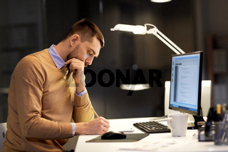 man with notepad working on code at night office