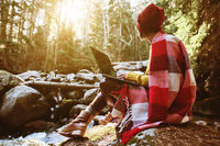 A toned portrait of a freelancer hipster girl with glasses and a stylish cap dressed in a blanket with a laptop kneeling sitting on a rock in a coniferous forest next to a stormy mountain river in warm sunlight. The concept of freelancing work at a distan
