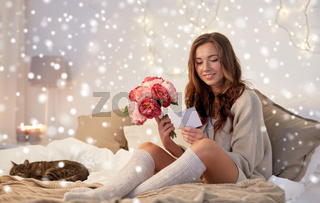 happy woman with flowers and greeting card at home