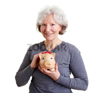 Seniorin hält Sparschwein