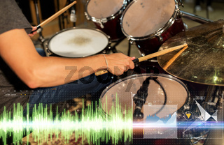 male musician playing drum kit at concert