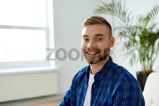 portrait of happy smiling young man at office