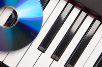 CD Laying on Piano Keyboards Abstract