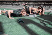 Sportive man and woman doing push ups.