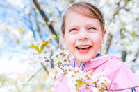 little laughing girl squinting eyes on a spring background with blooming cherries
