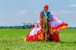 Paraglider carrying mattress flyer in meadow