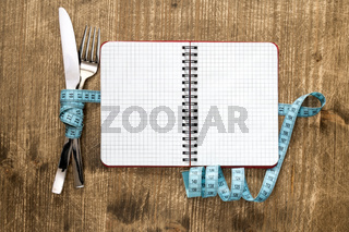 Cutlery tied with measuring tape and blank notebook