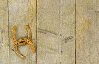 Zwei rostige Hufeisen hängen zusammen an einer Holzwand