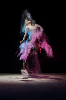 Young girl jumping in color dust cloud in studio