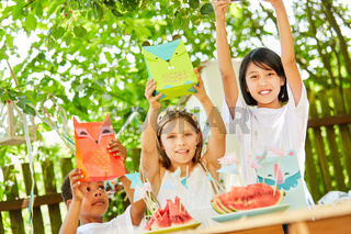 Kinder halten Tüten mit Geschenken hoch