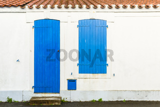 House facade with blue blinds and door