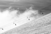 Snow off-piste ski slope and silhouette of chair-lift in fog