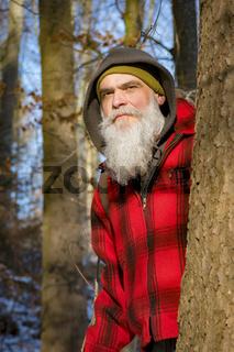 a gray bearded lumberjack in the woods