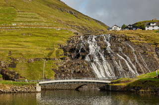 Village and beautiful waterfall landscape of Faroe Islands, Denmark