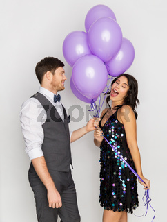 happy couple with ultra violet balloons at party