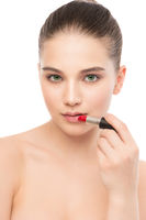 Young brunette woman with perfect clean face applying lipstick. Isolated on a white.