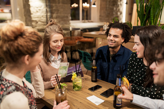 friends with drinks, money and bill at bar
