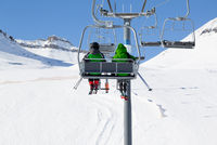 Two skiers on chair-lift and snow ski slope