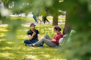 Young man and woman tourists with backpacks have rest in the park